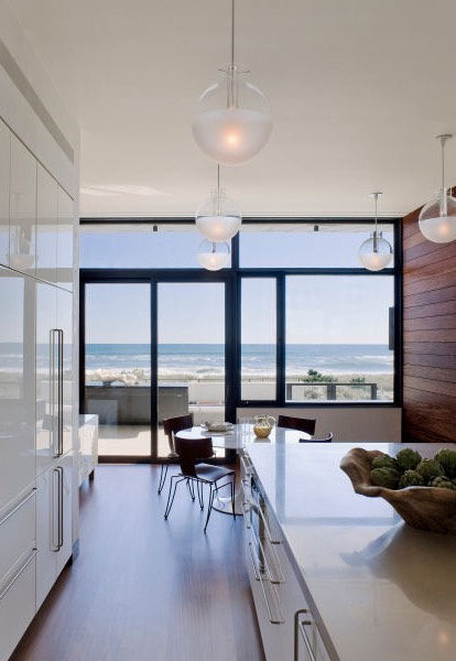 View of beautiful blue ocean through floor to ceiling windows from dining room