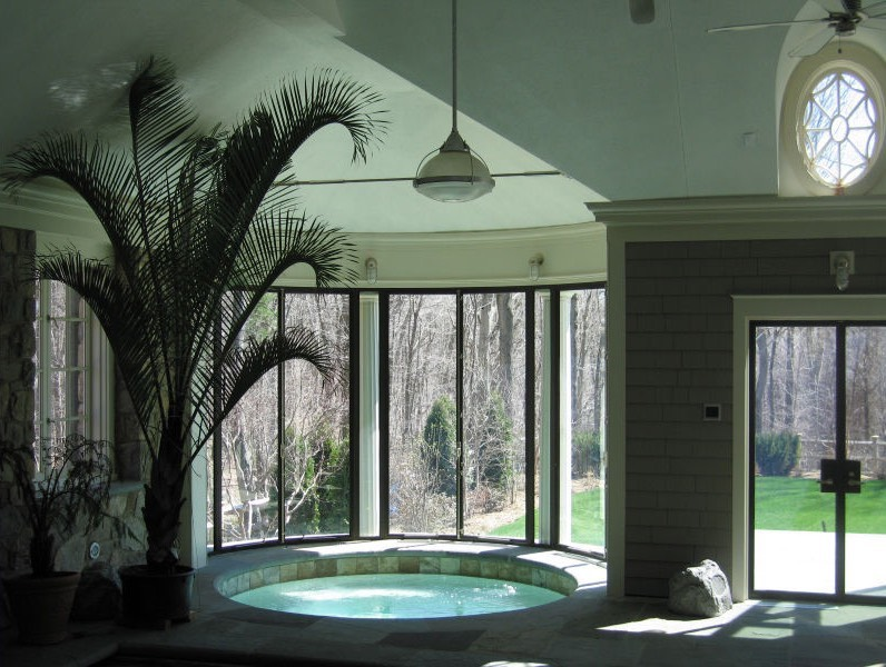 Indoor hot tub oasis with window patio doors